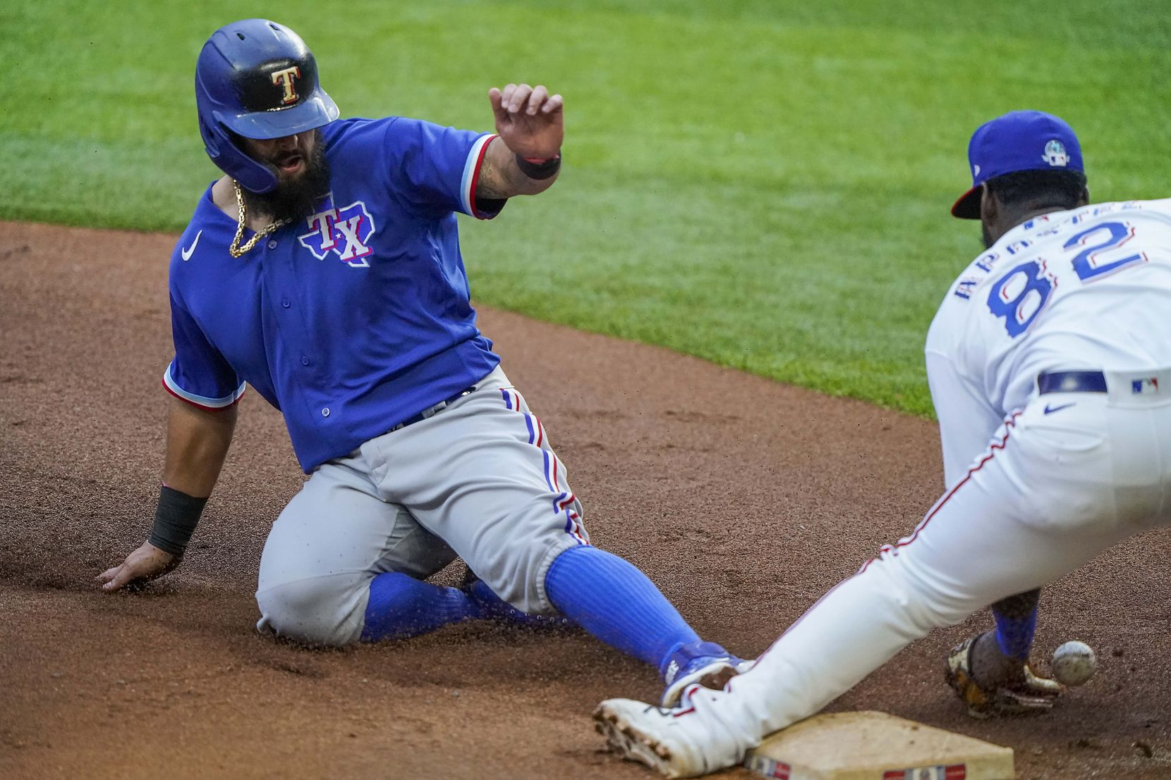 Second baseman Rougned Odor is safe at third base with a steal as the ball gets away from infielder Sherten Apostel in an intrasquad game during Texas Rangers Summer Camp at Globe Life Field on Friday, July 17, 2020.