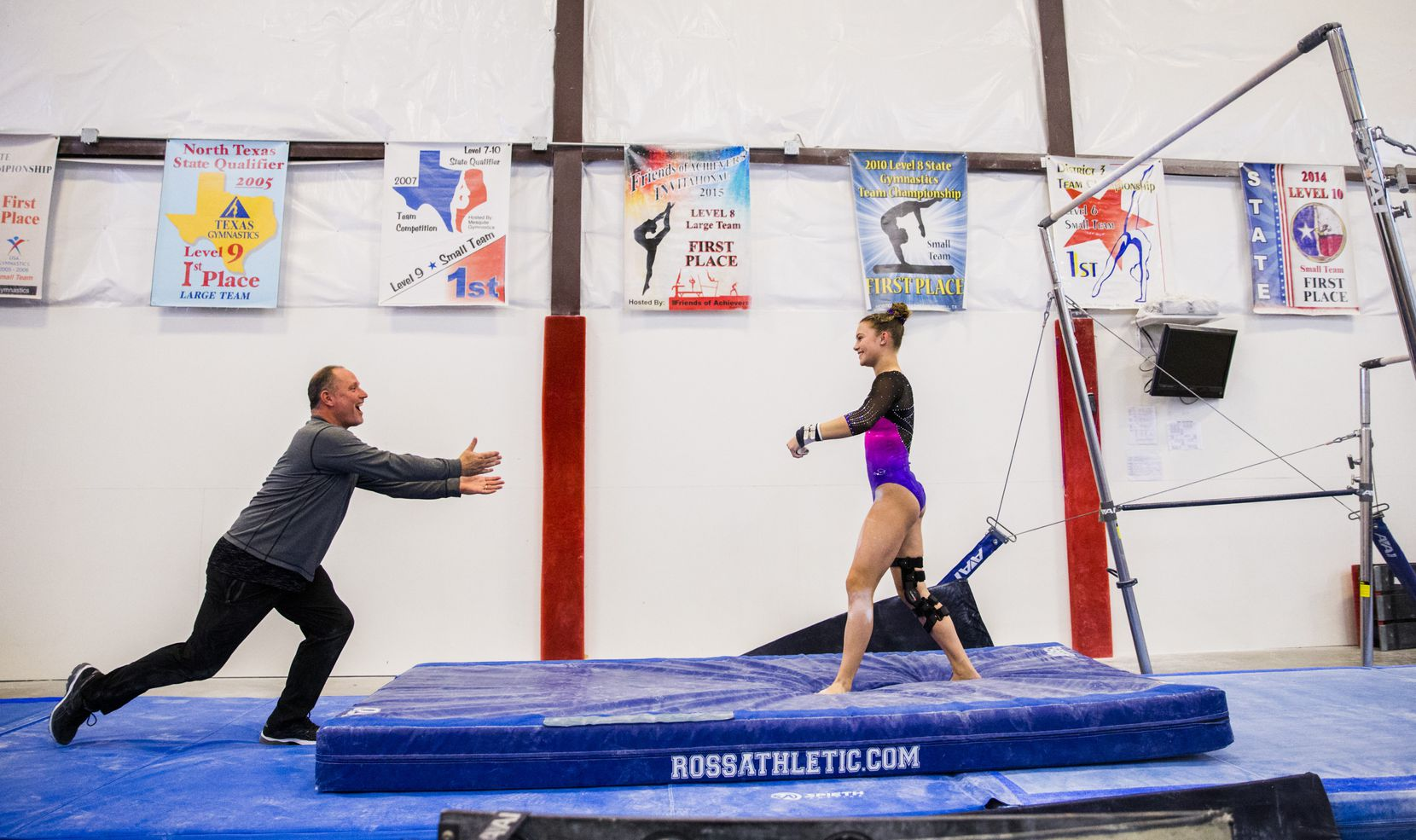 U.S. Gold Gymnastics coach Bobby Dombrowski runs to congratulate Hannah Ewing, 18, on her bar routine during the Zenith Winter Classic meet on Saturday, February 24, 2018 at Zenith Gymnastics in McKinney, Texas. (Ashley Landis/The Dallas Morning News)
