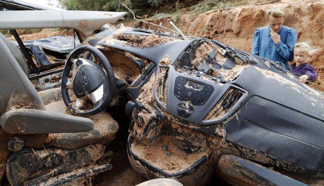 Una mujer y un niño examinan los restos de un vehículo que fue arrastrado por una inundación repentina en Hilldale, Utah. Al menos 16 personas murieron. (AP/MICHAEL CHOW)