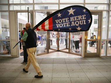 Election official Jimmy Murphy carried off a sign at the conclusion of Dallas County's early voting period on Friday at the George L. Allen Sr. Courts Building in downtown Dallas. (Andy Jacobsohn/Staff Photographer)