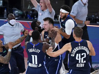 Luka Doncic #77 of the Dallas Mavericks celebrates with teammates after making a game-winning 3-point basket against the Los Angeles Clippers during overtime of Game Four of the first round of the playoffs between the Los Angeles Clippers and the Dallas Mavericks at the AdventHealth Arena at the ESPN Wide World Of Sports Complex on August 22, 2020 in Lake Buena Vista, Florida.