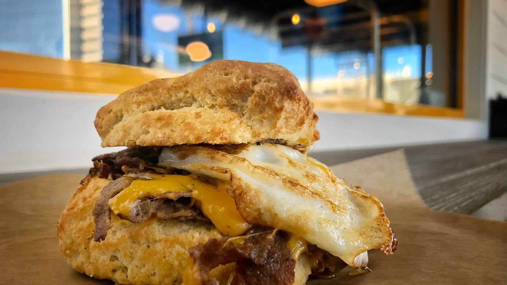The Biscuit Bar serves a Steak & Egg biscuit, made with sliced ribeye, an egg over easy and melted cheddar cheese.