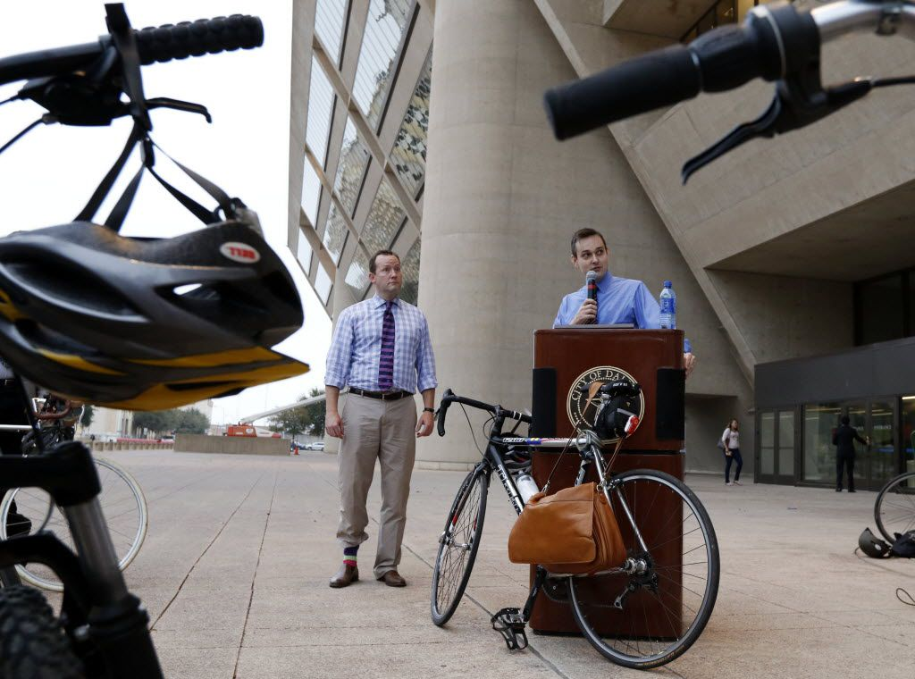 City Council member Philip Kingston looks on as council member Scott Griggs speaks after a group bike from Main Street Garden Park  to Dallas City Hall.