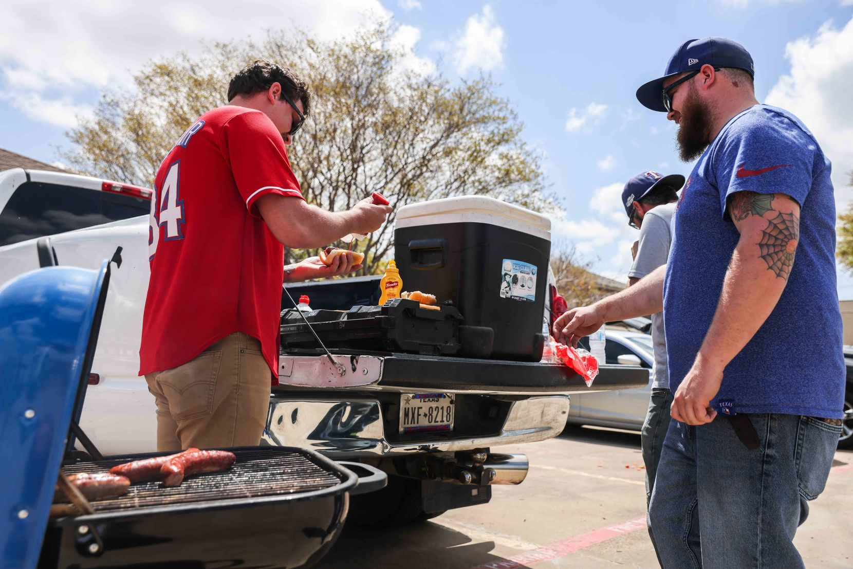 From left Dylan Huerta, Beau Wyse and Kary Krafve get a meal outside the Globe Life Field before the game between Texas Rangers and Toronto Blue Jays on opening day in Arlington, Texas on Monday, April 5, 2021. (Lola Gomez/The Dallas Morning News)