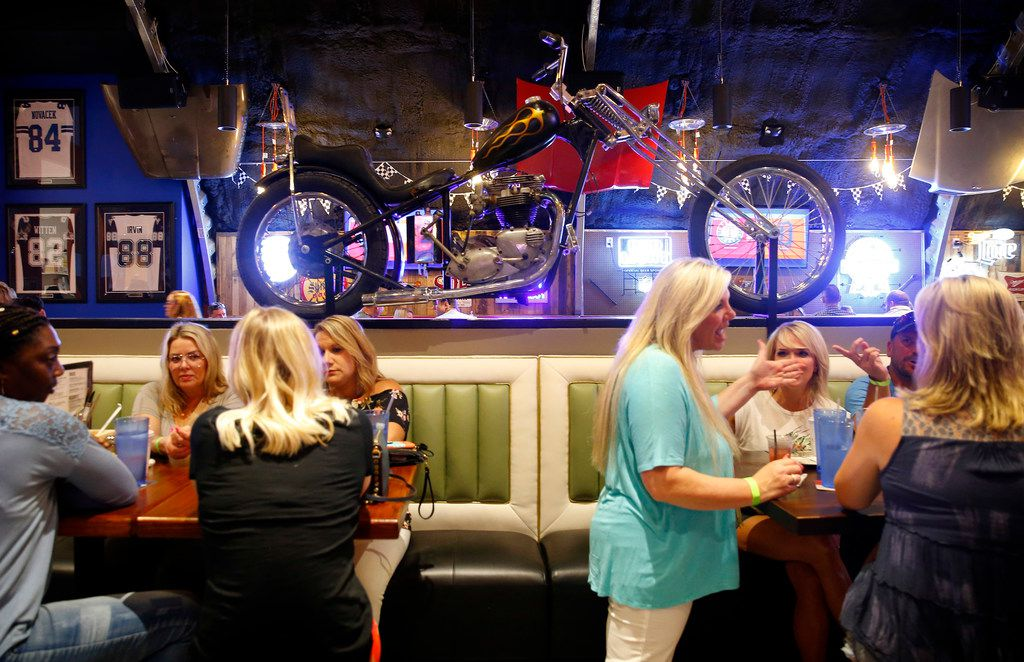 A chopper parked in the bar is part of the decor at ChopShop Live in Roanoke, Texas, Friday, July 6, 2018. (Tom Fox/The Dallas Morning News)