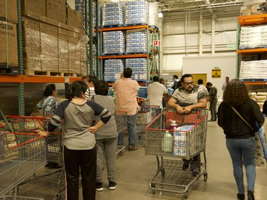 At a Costco in Ciudad Juarez, Mexico, people line up to receive rations of the store's stock of toilet paper, water bottles and Lysol disinfectant sprays, limiting the amount each member can purchase Monday, March 16.