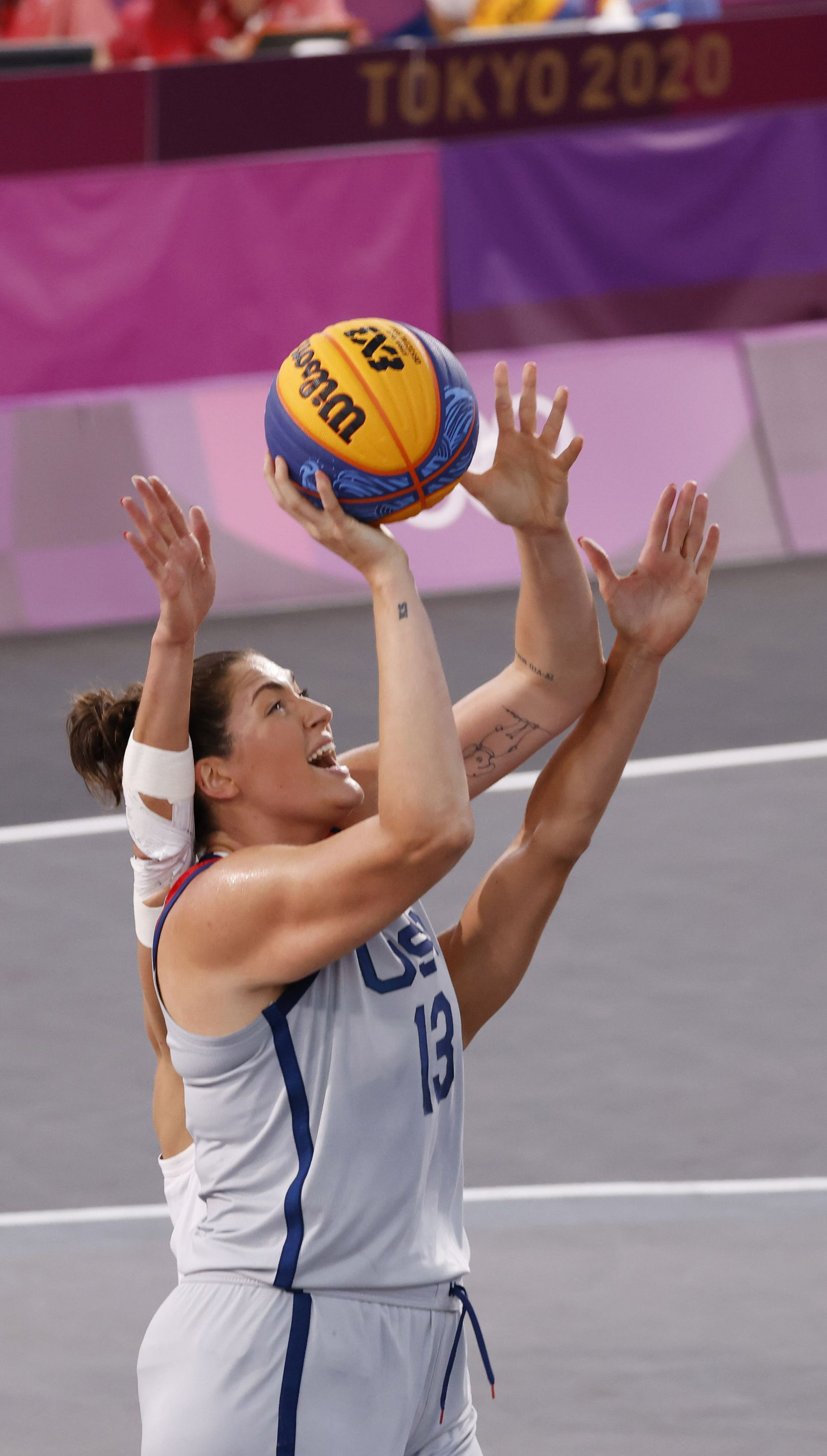 USA's Stefanie Dolson (13) shoots as she is defended by France's Laetitia Guapo (12) during a 3x3 women's basketball match during the postponed 2020 Tokyo Olympics at Aomi Urban Sports Park on Saturday, July 24, 2021, in Tokyo, Japan. USA defeated France 17-10 in the game. (Vernon Bryant/The Dallas Morning News)