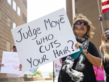 Ellen Lopez holds a sign as she waits for Shelley Luther to be released from Dallas County Jail on May 7, 2020. Lopez called Luther her hero for being courageous and sticking to her principles.