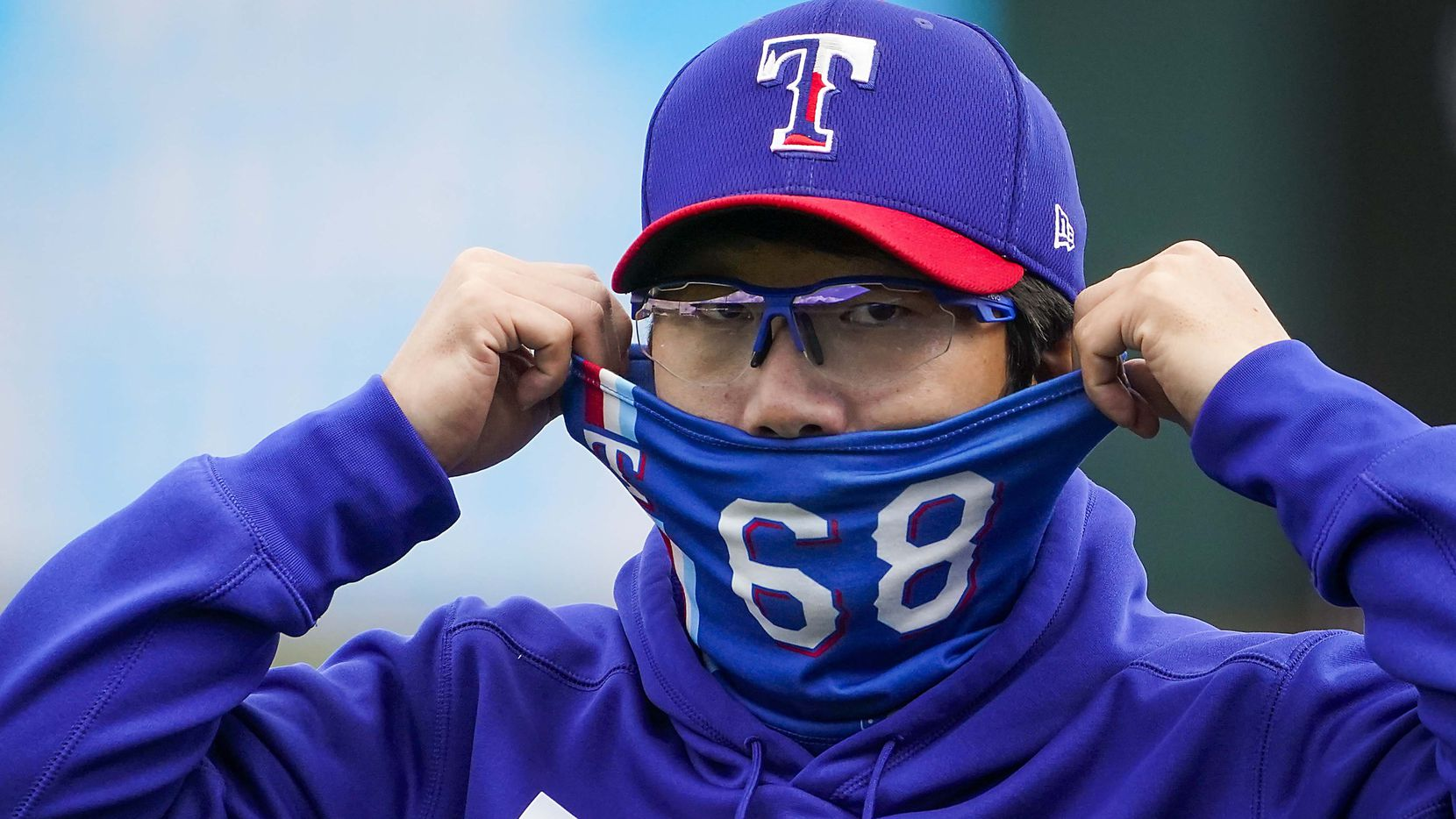Texas Rangers pitcher Hyeon-jong Yang adjusts his face covering before of a spring training game against the San Diego Padres at Surprise Stadium on Thursday, March 4, 2021, in Surprise, Ariz.