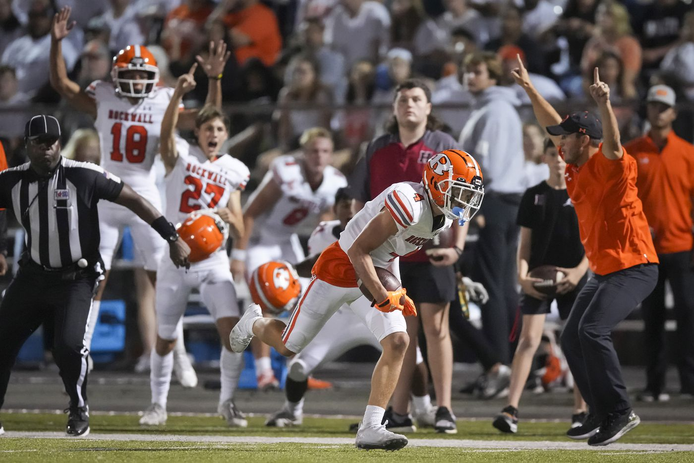 The Rockwall bench erupts as defensive back Tre Carter (4) recovers an onside kick during the second half of a District 10-6A high school football game against Rockwall-Heath at Wilkerson-Sanders Stadium on Friday, Sept. 24, 2021, in Rockwall.  Rockwall-Heath won the game 79-71 in double overtime.
