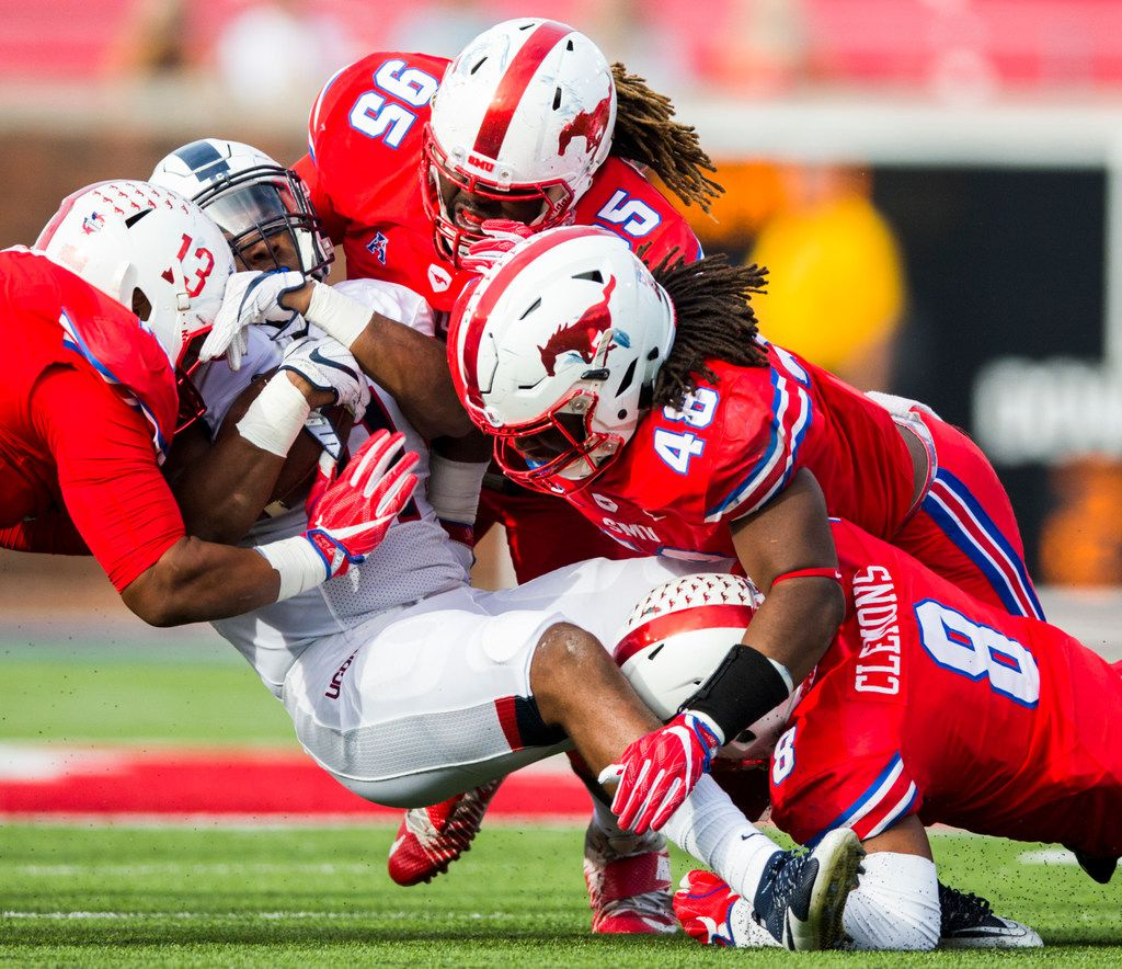 Southern Methodist Mustangs defensive lineman Tyeson Neals (13), defensive tackle J.T. Williams (95), linebacker Anthony Rhone (48) and defensive back Rodney Clemons (8) tackle Connecticut Huskies running back Nate Hopkins (11) during the third quarter of a football game between the University of Connecticut and SMU Texas on Saturday, September 30, 2017 at SMU's Ford Stadium in Dallas. (Ashley Landis/The Dallas Morning News)