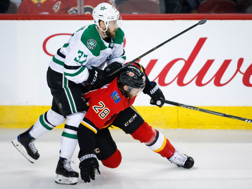 Dallas Stars' Justin Dowling, left, checks Calgary Flames' Elias Lindholm during the first period of an NHL hockey game Wednesday, March 27, 2019, in Calgary, Alberta. (Jeff McIntosh/The Canadian Press via AP)