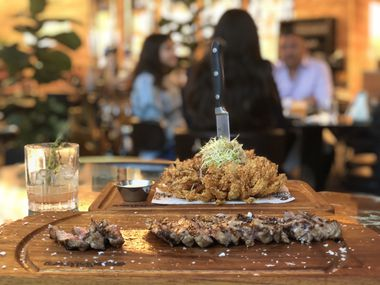 The Istanbul steak at Nusr-Et in Dallas costs $100. When he's in town, butcher Salt Bae (a.k.a., Nusret Gökçe) will slice and salt steaks tableside. The onion flower costs $19 and the Light My Fire cocktail — which is lit on fire at the table — costs $25.
