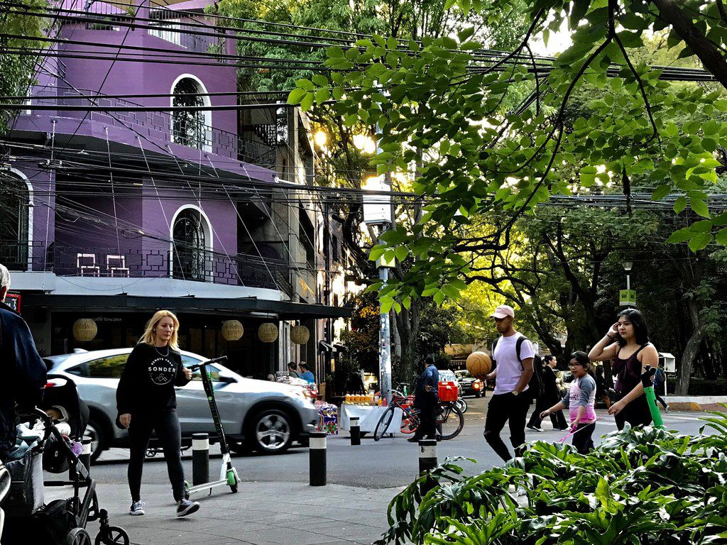 La Roma and La Condesa, Mexico's hipster neighborhoods are divided by an avenue and are considered rivals.  Pedestrians enjoy a January afternoon.