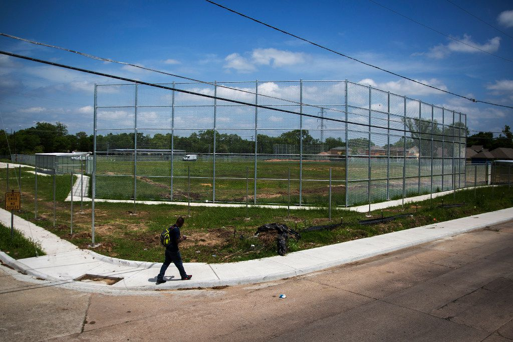 A man walks past a vacant lot that is being turned into a baseball field at at the corner of Meadow St. and Birmingham Ave., a about a block away from Madison High School, on Tuesday, April 25, 2017, in Dallas.   (Smiley N. Pool/The Dallas Morning News)