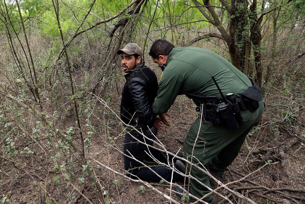 In this Thursday, March 14, 2019, photo, an agent apprehends a person suspected of having entered the U.S. illegally near McAllen, Texas. While many adults crossing the border on their own in the Rio Grande Valley try to flee agents, most migrant parents and children wait to surrender so they can legally seek asylum in the U.S.