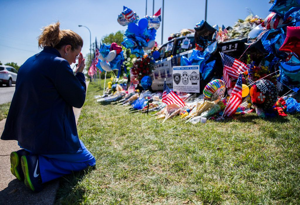 Shari Stout prayed next to a makeshift memorial for Dallas police Officer Rogelio Santander outside the northeast patrol substation. Santander was shot and killed outside of a Home Depot in Lake Highlands.
