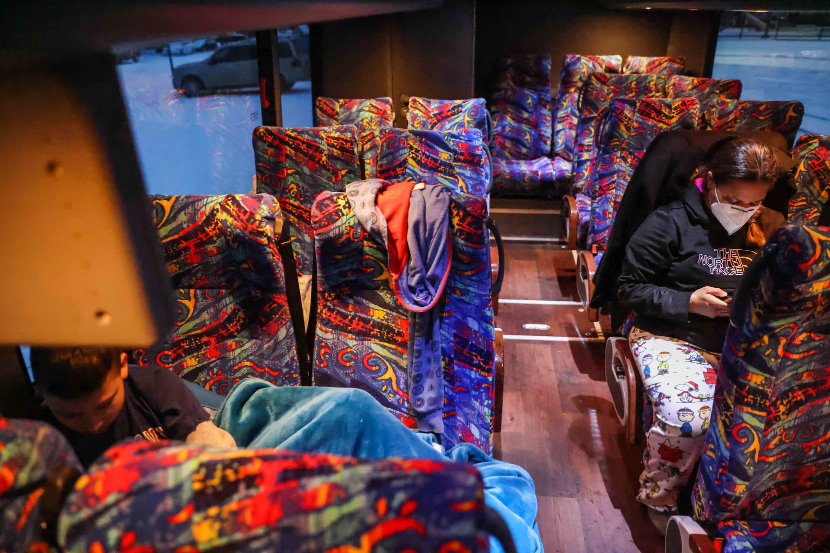Marleny Almendarez, de 38 años, revisa su teléfono mientras su hijo Aaron, de 11 años y quien se encuentra dentro espectro del autismo, trata de acomodarse al interior de un autobús con calefacción.