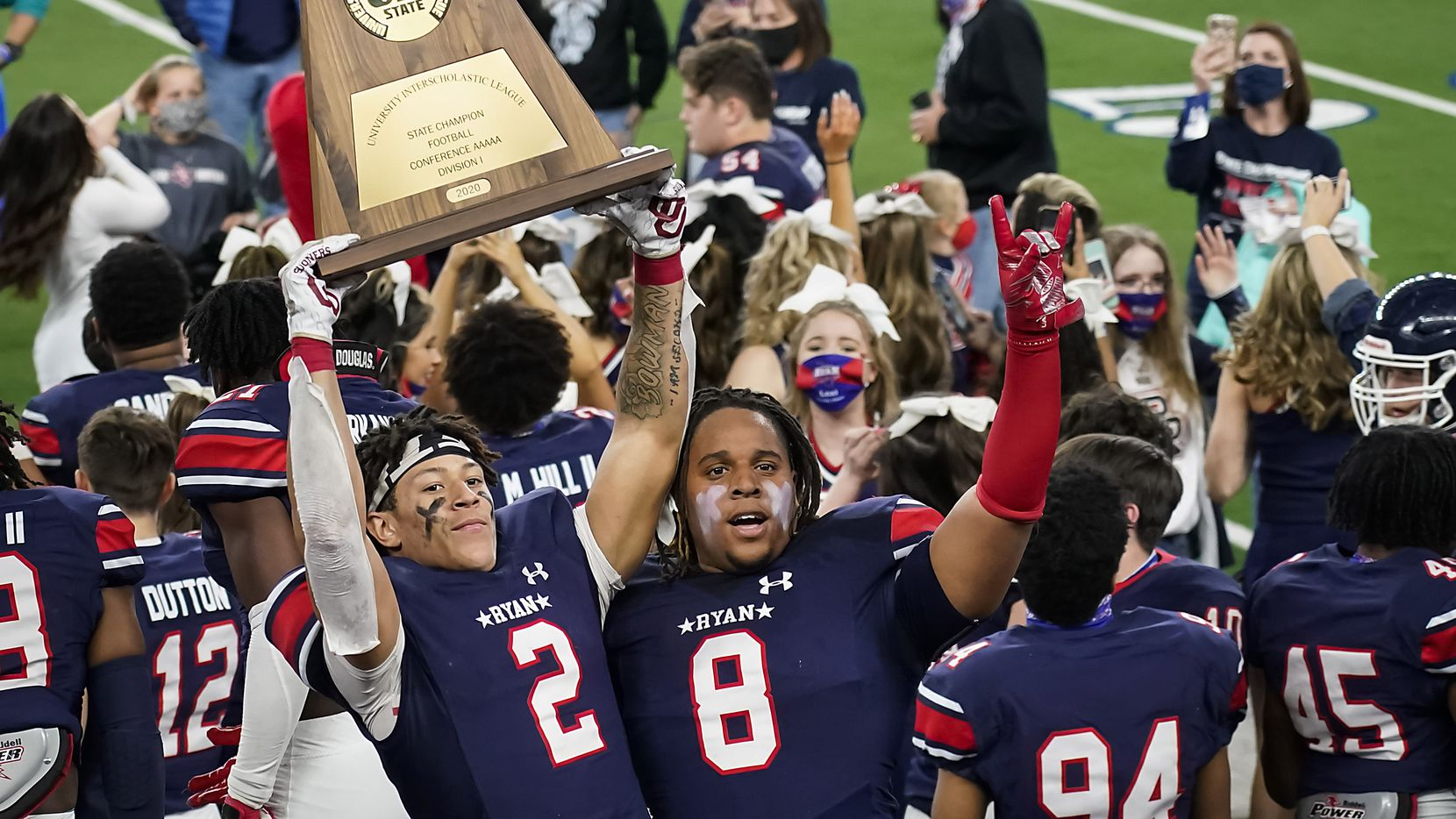 Denton Ryan wide receiver Billy Bowman Jr. (2) hoists the championship trophy with teammate Jay Sheppard (8) as players celebrate a 59-14 victory over Cedar Park to win the Class 5A Division I state football championship game at AT&T Stadium on Friday, Jan. 15, 2021, in Arlington, Texas. (Smiley N. Pool/The Dallas Morning News)
