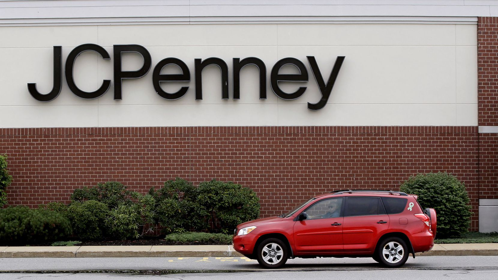Photo taken on Friday, July 10, 2015 as a car drives through an empty J. C. Penney department store parking lot at the Hanover Mall in Hanover, Mass.  This store closed in April 2015. (AP Photo/Stephan Savoia)
