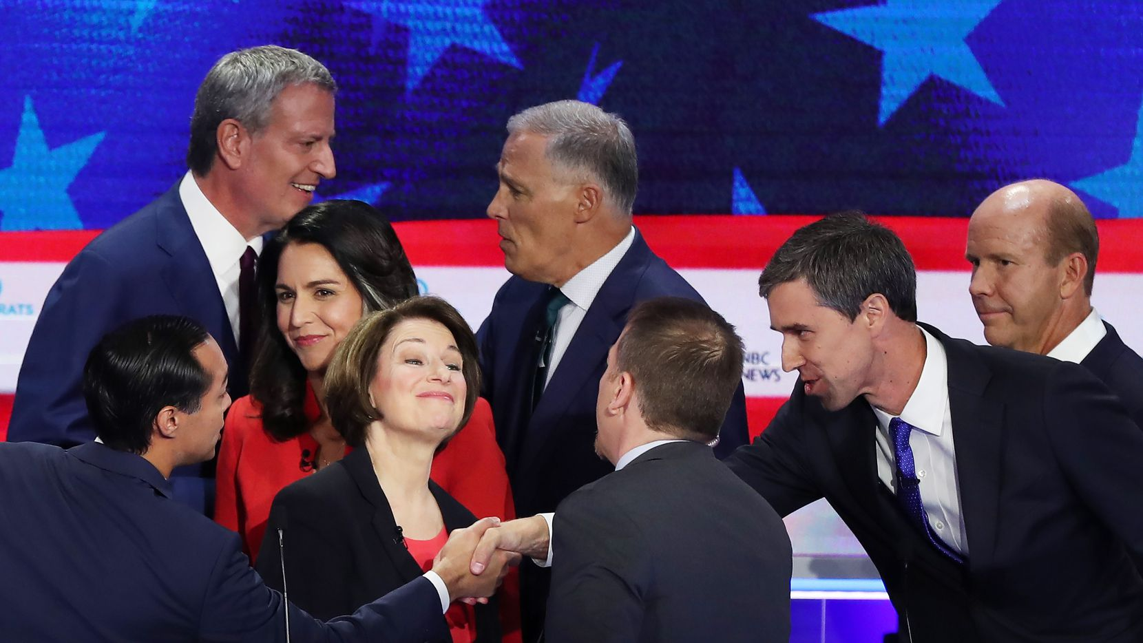 Former U.S. housing secretary Julian Castro (far left) and former Texas congressman Beto O'Rourke (2nd from right) reach to shake hands after the first night of the Democratic presidential debate on June 26, 2019 in Miami,