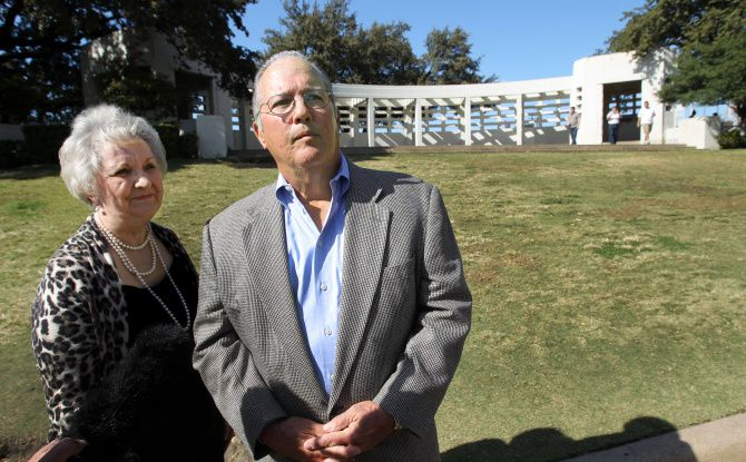 Gayle and Bill Newman stand near the spot where, 49 years ago, they shielded their small children after shots were fired that killed President John F. Kennedy,