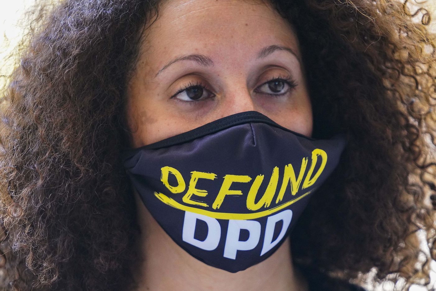 Sara Mokuria of Mothers Against Police Brutality wears a face mask reading 'Defund DPD' during a rally commemorating Juneteenth at Dallas City Hall on Friday, June 19, 2020.