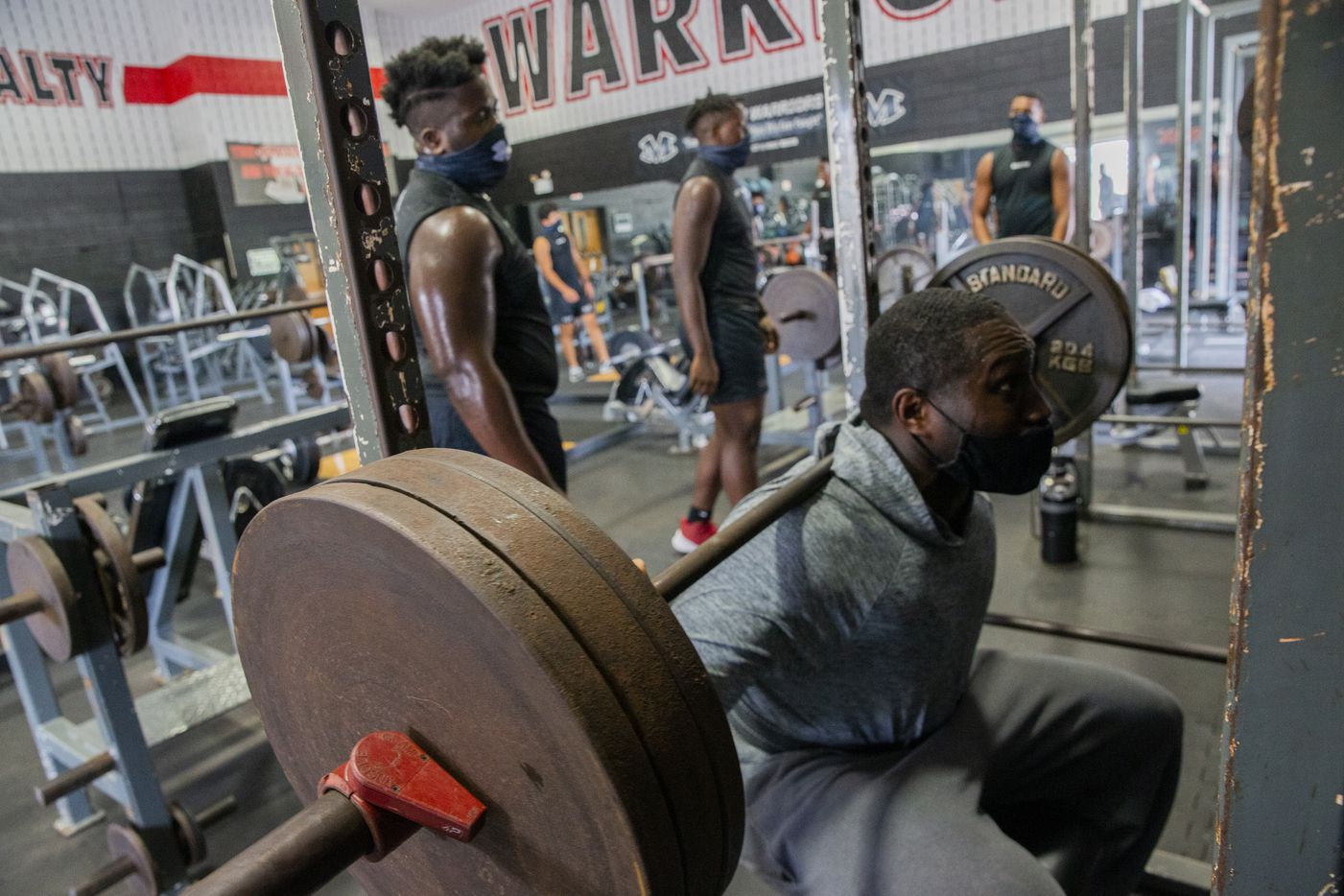 "Homicide Sergeant Brian Jones from the Arlington Police Department squats as he works out with Arlington Martin Defensive tackle Marquis Evans (left) during their workout at the school's gym as part of the ""Coach 5-0"" program on Monday, Sept. 21, 2020 in Arlington. (Juan Figueroa/ The Dallas Morning News)"