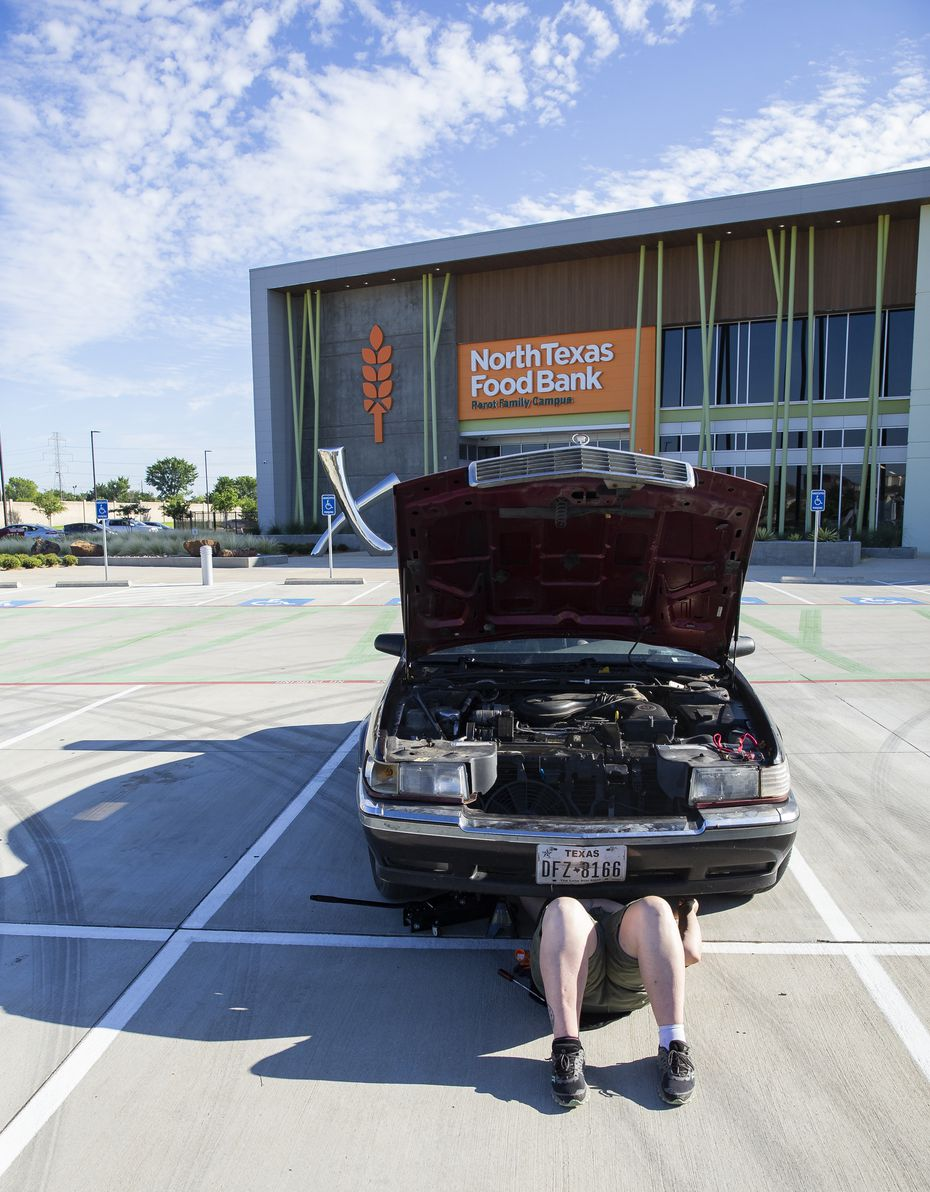 Elise Earnhart Bigony repairs her stalled car after donating food at North Texas Food Bank in Plano on Monday, June 8, 2020.