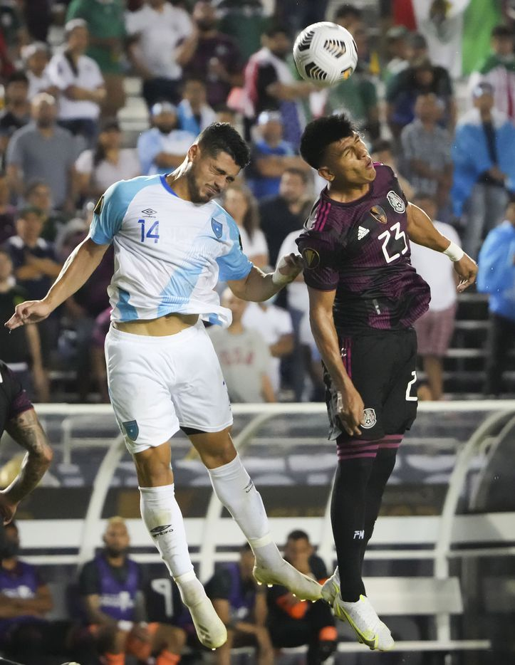 Guatemala forward Darwin Lom (14) fights for a header against Mexico midfielder Jesús Gallardo (23)during the first half of a CONCACAF Gold Cup Group A soccer match at the Cotton Bowl on Wednesday, July 14, 2021, in Dallas.