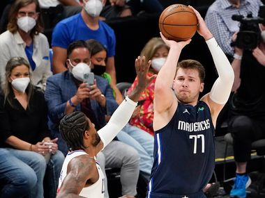 Dallas Mavericks guard Luka Doncic (77) shoots over LA Clippers guard Paul George (13) during the second quarter of an NBA playoff basketball game at American Airlines Center on Friday, May 28, 2021, in Dallas. (Smiley N. Pool/The Dallas Morning News)