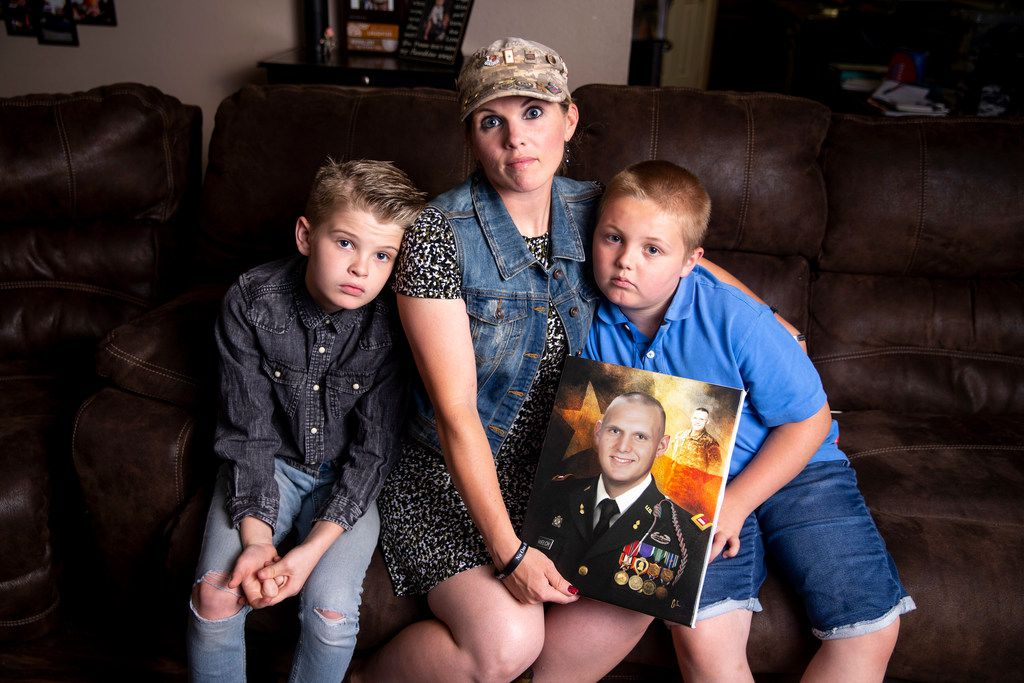 Aaden Welch, 11, left, along with his mother Becky Welch and his brother, Robby Welch, 9, right, poses for a photograph with a portrait of their father, Army 1st Lt. Rob Welch, in their home in Wylie. A provision in the 2017 tax overhaul caused the Welch family's taxes to increase from about $400 to $2200 this year on the survivor benefits they've receive since Rob was killed in Afghanistan in 2011.