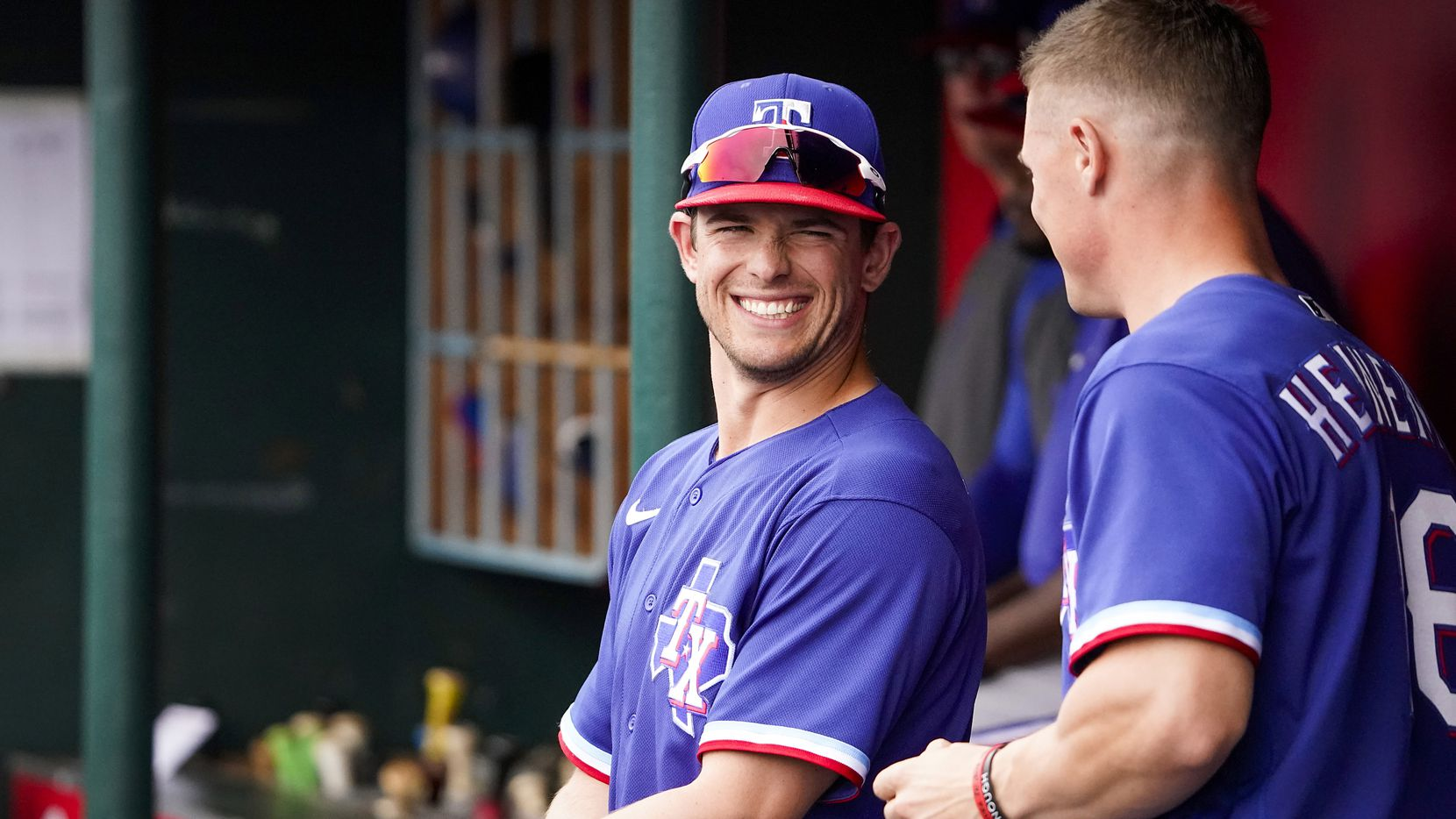FILE - Rangers infielder/outfielder Nick Solak laughs with outfielder Scott Heineman in the dugout during the fourth inning of a spring training game against the Los Angeles Angels at Tempe Diablo Stadium on Friday, Feb. 28, 2020, in Tempe, Ariz.