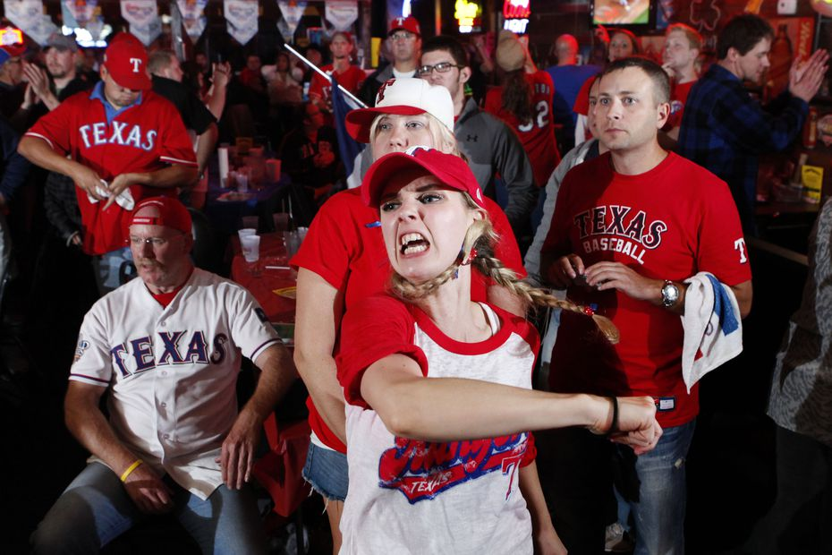 Texas Rangers baseball fan Lauren Schrimsher, center, reacts with sadness and anger as things turn badly for the Rangers at the J. Gilligans sports bar during Game 6 of the World Series on Thursday, Oct. 27, 2011 in Arlington, Tx.