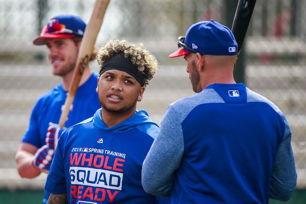 Texas Rangers outfielder Willie Calhoun talks with manager Chris Woodward between rounds of batting practice during a spring training workout at the team's training facility on Friday, Feb. 15, 2019, in Surprise, Ariz.. (Smiley N. Pool/The Dallas Morning News)