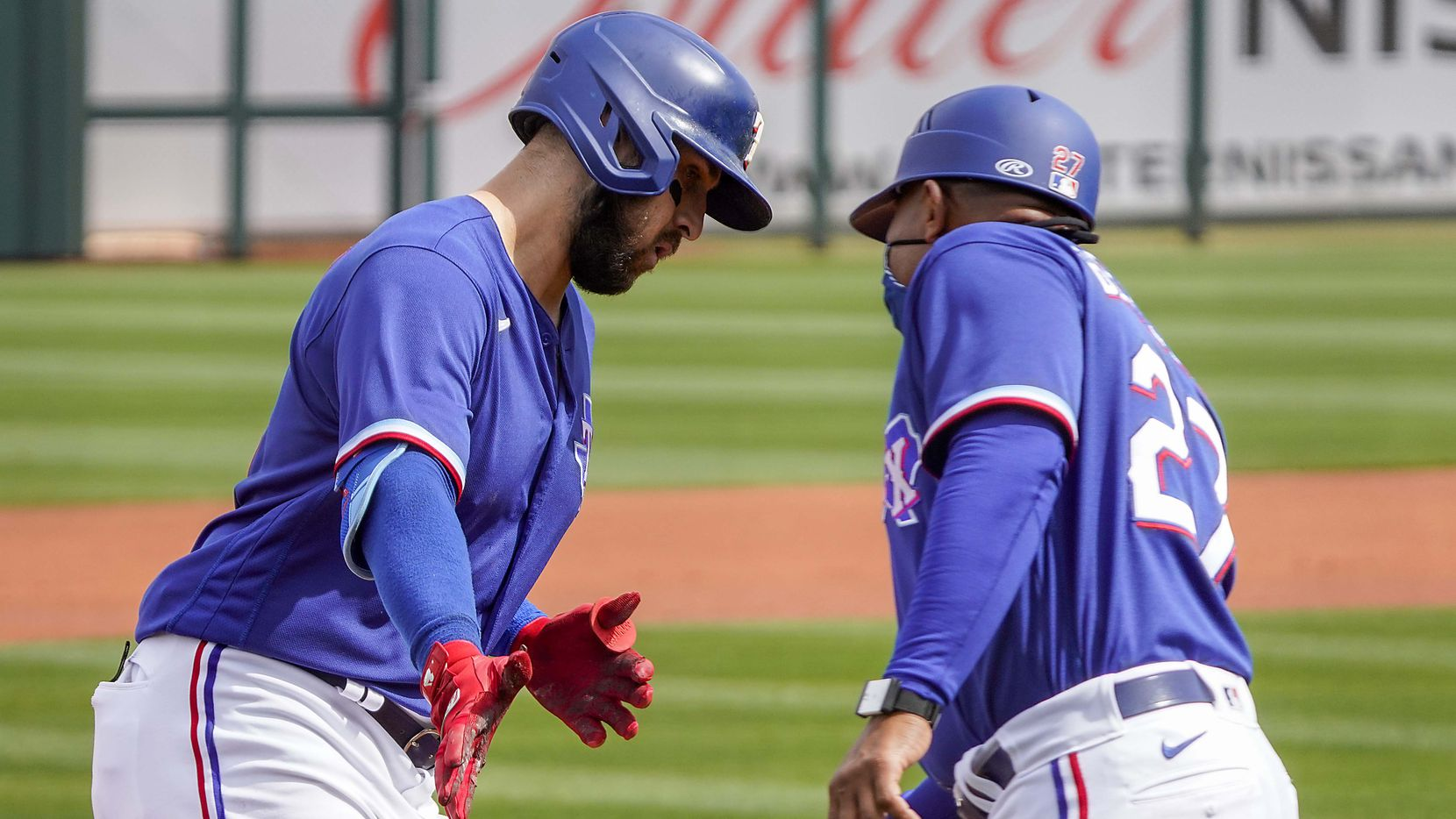 Texas Rangers outfielder Joey Gallo celebrates with third base coach Tony Beasley as he rounds the bases after hitting a solo home run off of Los Angeles Dodgers starting pitcher Walker Buehler during the first inning of a spring training game at Surprise Stadium on Sunday, March 7, 2021, in Surprise, Ariz.