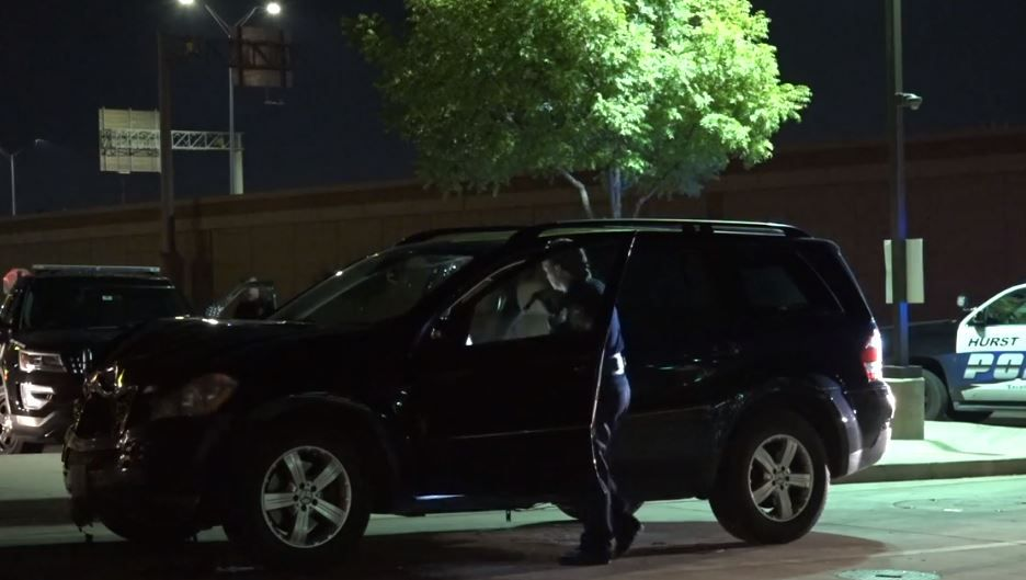 A Hurst police officer checks a damaged Mercedes SUV after it struck another vehicle on State Highway 183 Tuesday night.