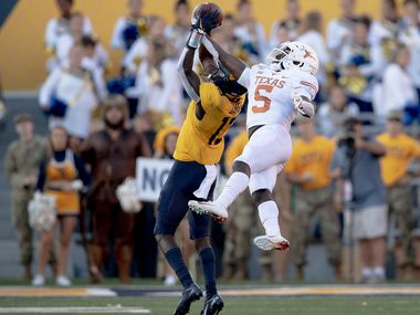 Texas defensive back D'Shawn Jamison (5) intercepts a pass intended for West Virginia wide receiver Sam James (13) during an NCAA college football game on Saturday, Oct. 5, 2019, in Morgantown, W.Va. (Nick Wagner/Austin American-Statesman via AP)