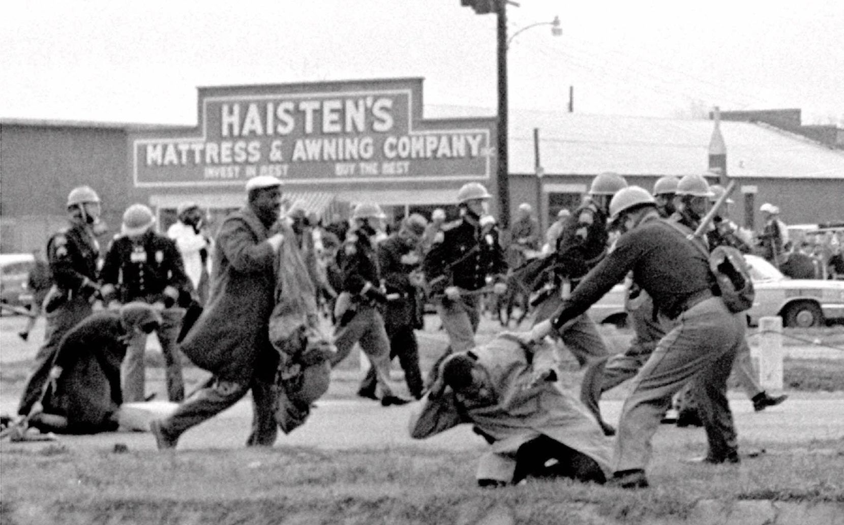 Alabama state troopers swing nightsticks to break up a civil rights voting march in Selma, Ala., on March 7, 1965. John Lewis, front right, of the Student Non-violent Coordinating Committee is put on the ground by a trooper.
