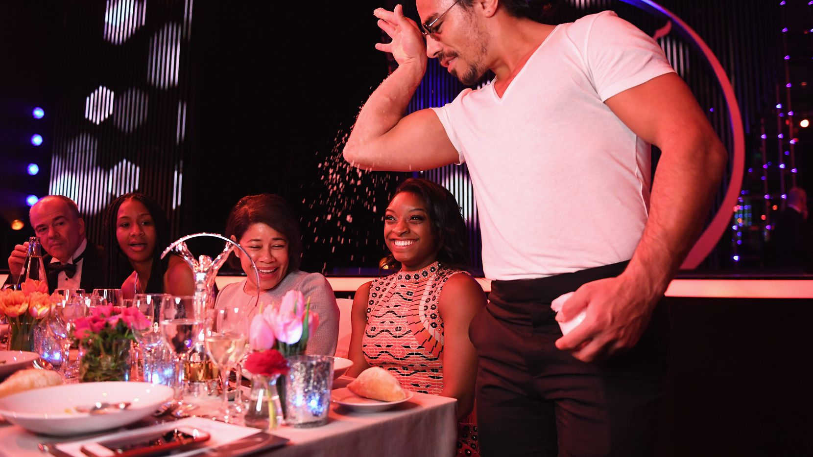 "Nusret Gokce, who goes by the nickname ""Salt Bae,"" adds salt to a plate in front of gymnast Simone Biles in 2017 in Monaco."