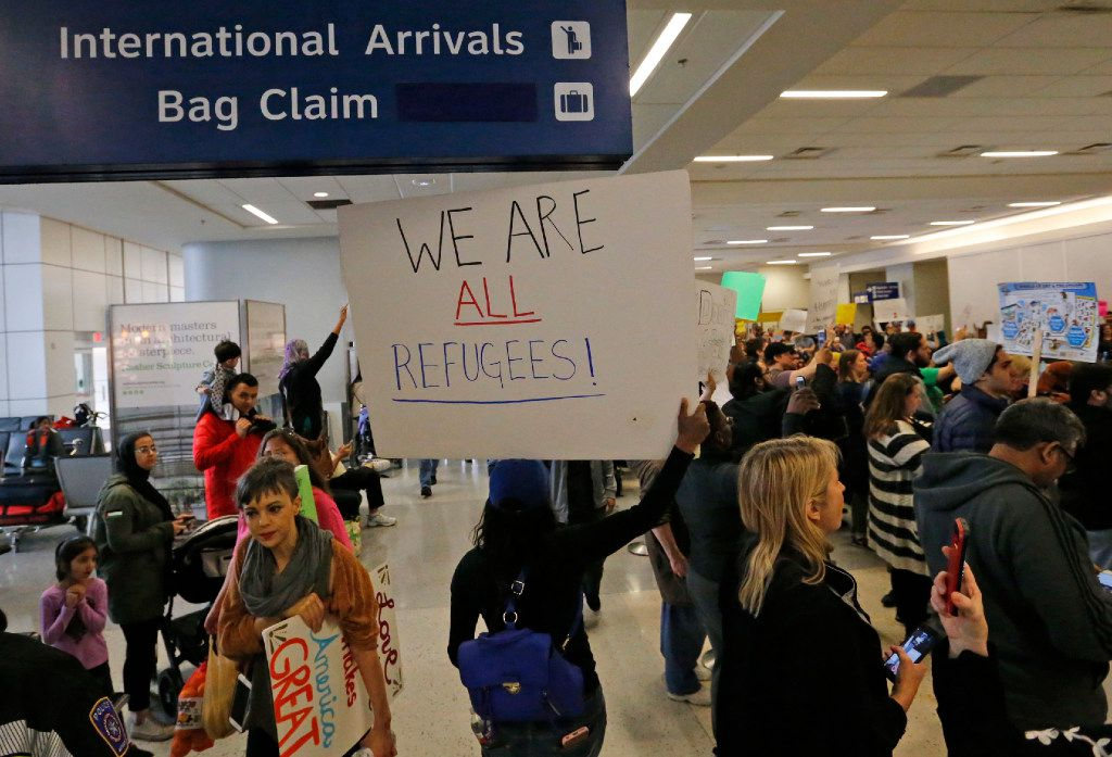 Protesters chant as they hold handmade signs at the international arrivals gate in Terminal D at DFW Airport on Sunday, January 29, 2017. (Louis DeLuca/The Dallas Morning News)