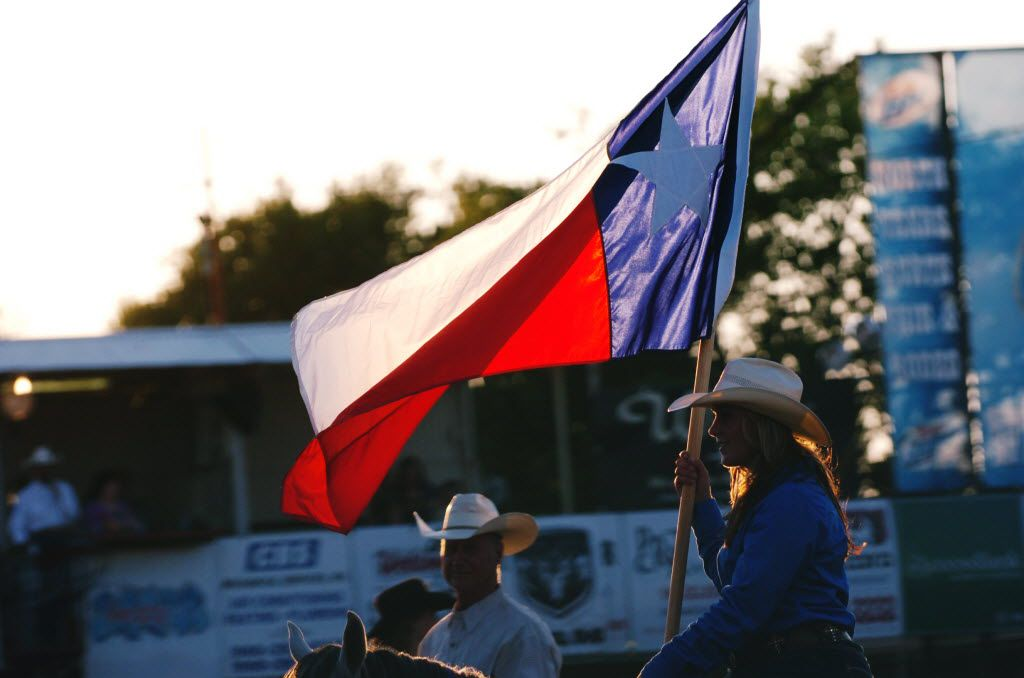 The Texas flag waved in the evening sun at the start of rodeo action at the 2013 North Texas Fair and Rodeo in Denton.