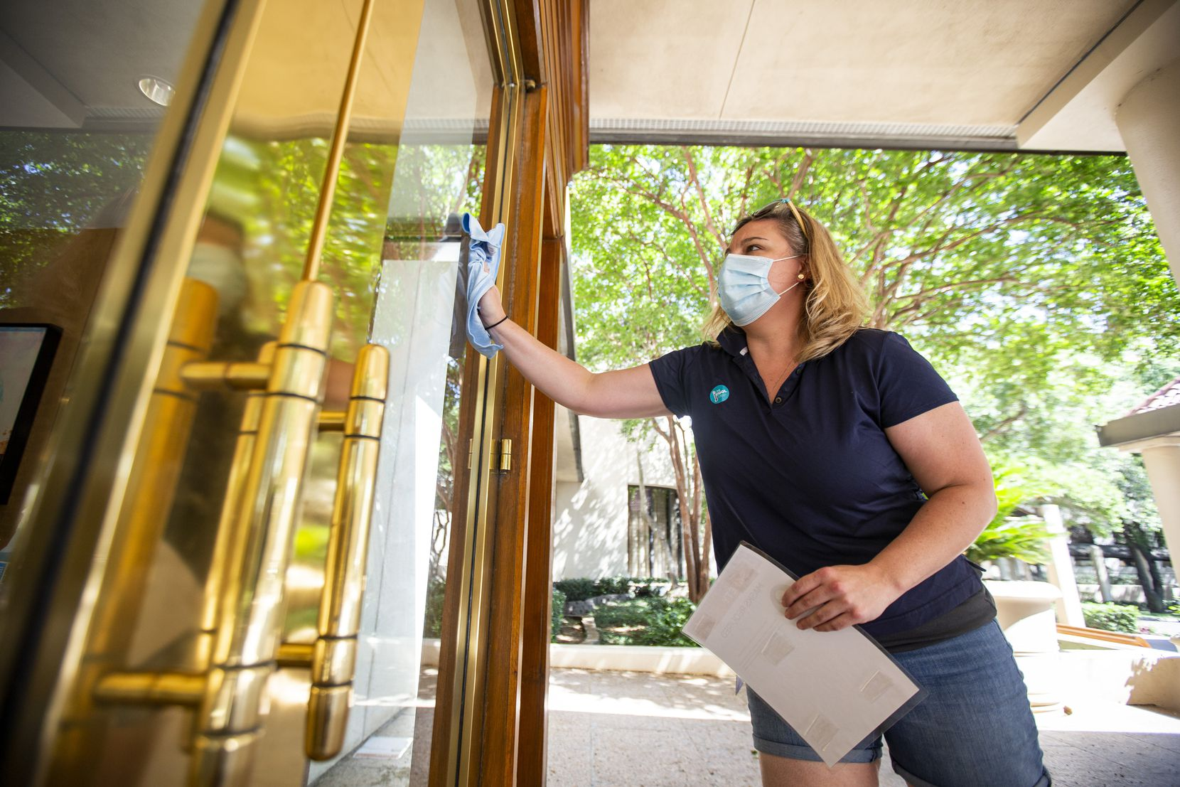 Director of Rooms Kelly Theus wipes down the front door at the Omni Las Colinas Hotel on Thursday.