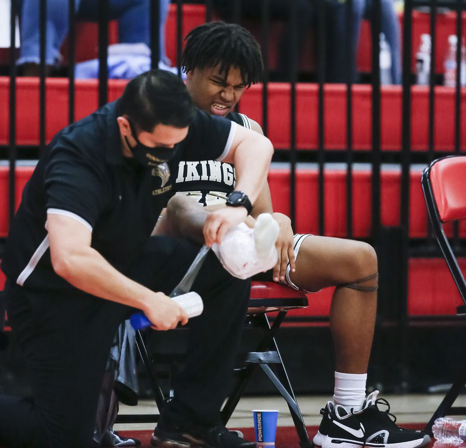 A trainer wraps ice onto Dallas Pinkston Ronald Bridgewater's right ankle after an injury during a Class 4A regional quarterfinal boys basketball playoff game against Dallas Carter at Skyline High School in Dallas, Saturday, February 27, 2021. Dallas Carter won 73-58.