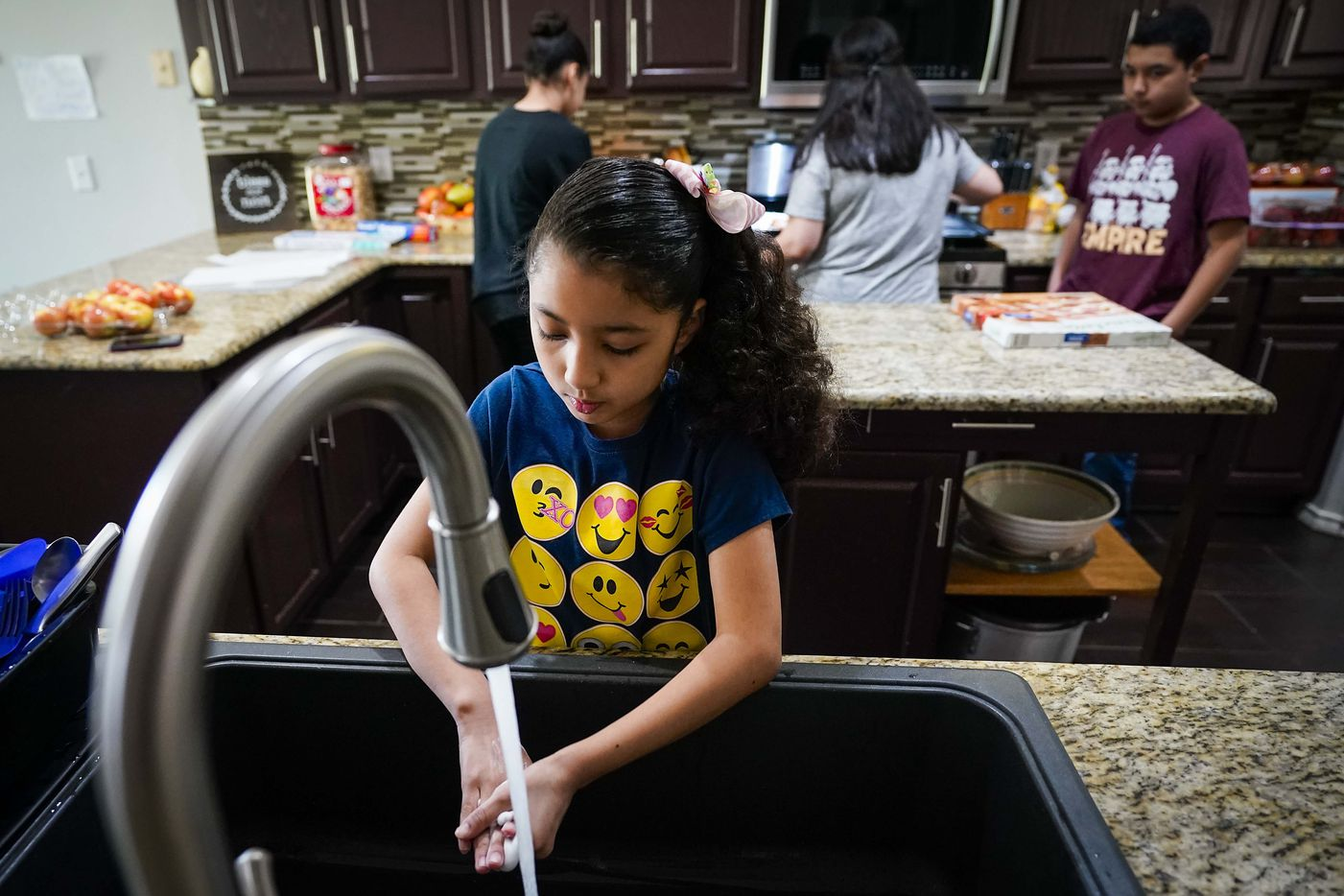 "Selena Cabrera, 9, washes her hands as her mother Nancy Segovia-Cabrera (background center), serves pizza for her brother Francisco (right) and sister Karla at lunch time at the family's home in Grand Prairie. The Cabrera family, like many around North Texas, suddenly has four youngsters at home with mom acting as ""principal"" making sure they all complete assignments as their school turns to distance learning in response to the new coronavirus."