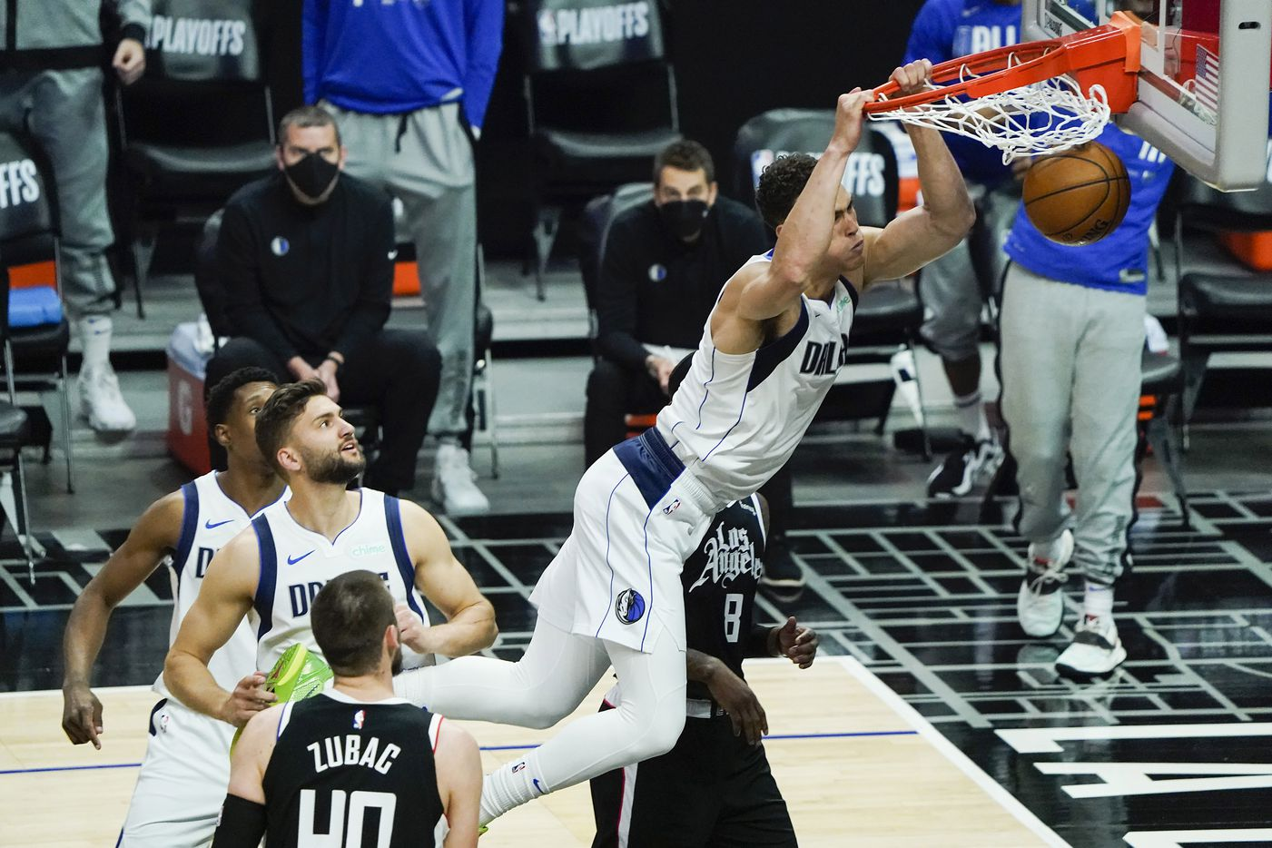 Dallas Mavericks center Dwight Powell (7) dunks the ball past LA Clippers forward Marcus Morris Sr. (8) and center Ivica Zubac (40) during the first half of an NBA playoff basketball game at the Staples Center on Wednesday, June 2, 2021, in Los Angeles.  (Smiley N. Pool/The Dallas Morning News)