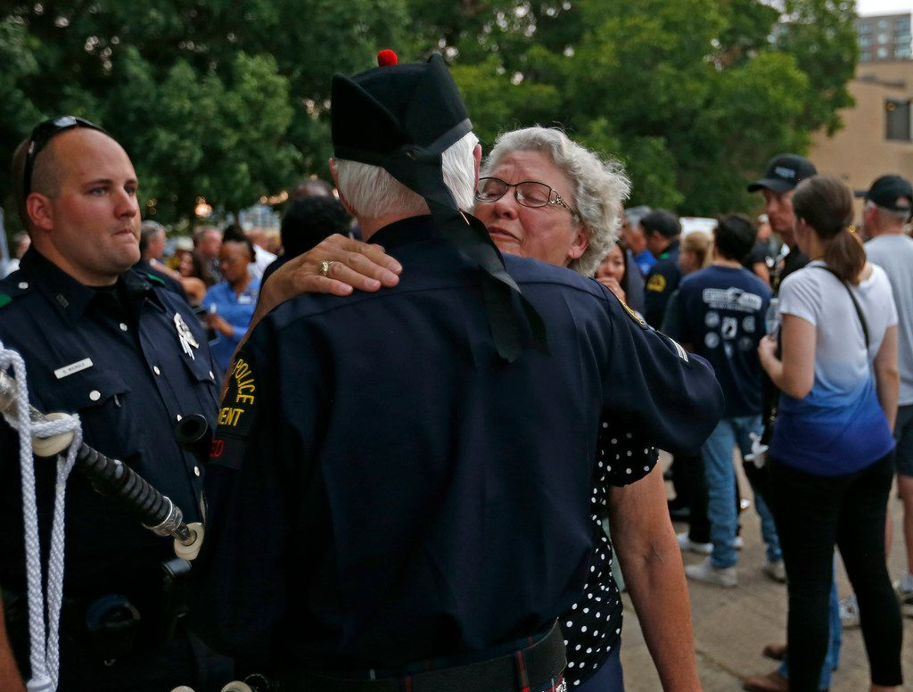 "Delores Givens, mother of Senior Cpl. Earl ""Jamie"" Givens got a hug from retired Dallas police detective Don Casey during a candlelight vigil for her son on Monday."