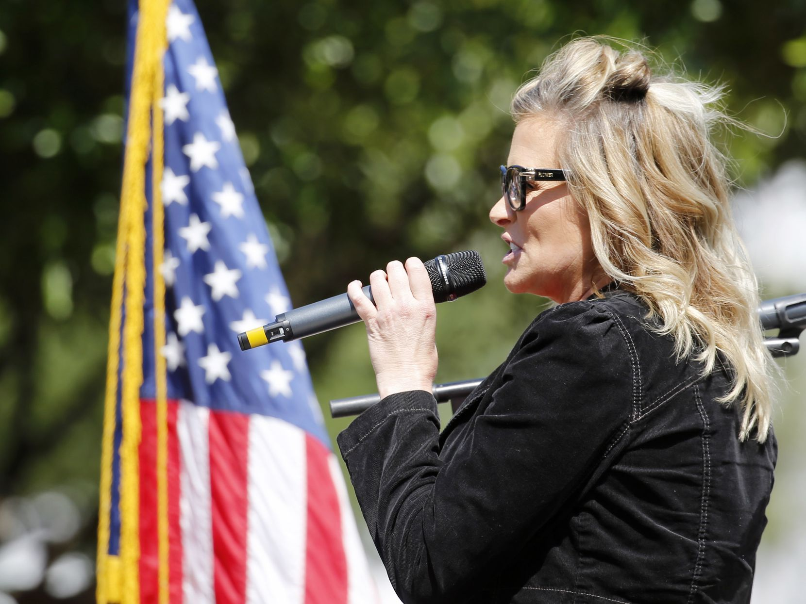 Business owner Shelley Luther addressed the crowd during an Open Texas rally Saturday outside Frisco City Hall.
