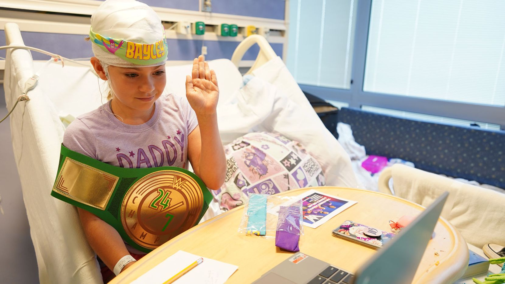 A young patient holding a WWE championship belt on a virtual Zoom call with WWE stars Montez Ford, Angelo Dawkins and Bianca Belair from Children's Medical Center Dallas.