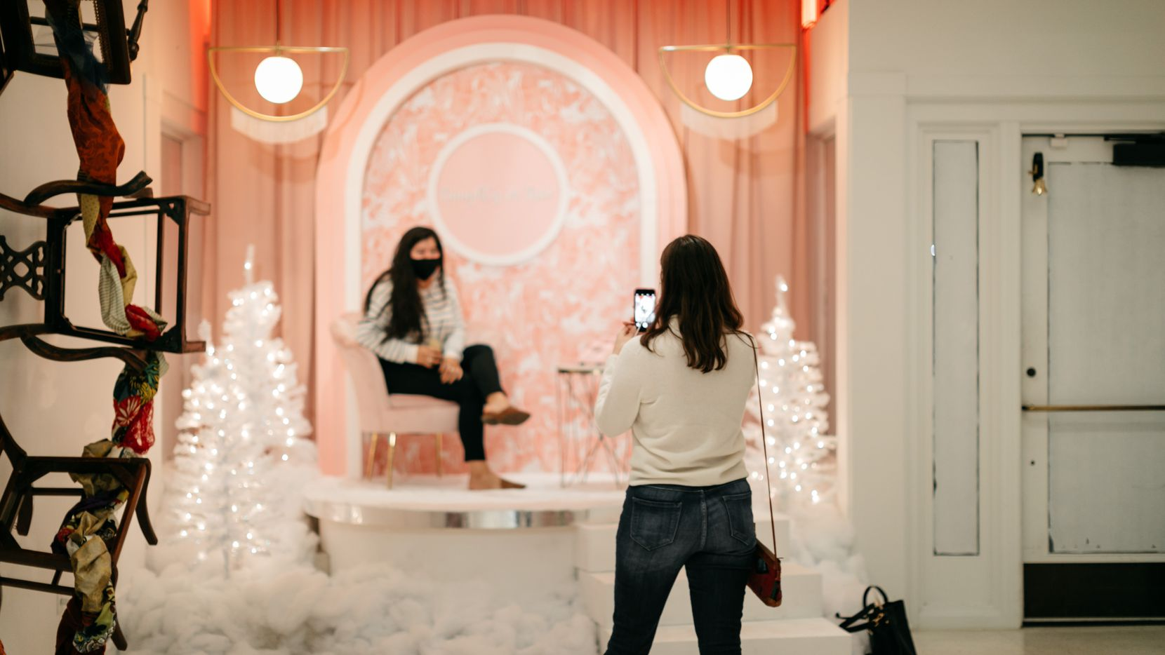 "An exhibit attendee takes a photo of someone sitting in the ""I'll Never Tell"" installation at the interactive ""Cheer!"" exhibit at the Joule Hotel in Dallas."